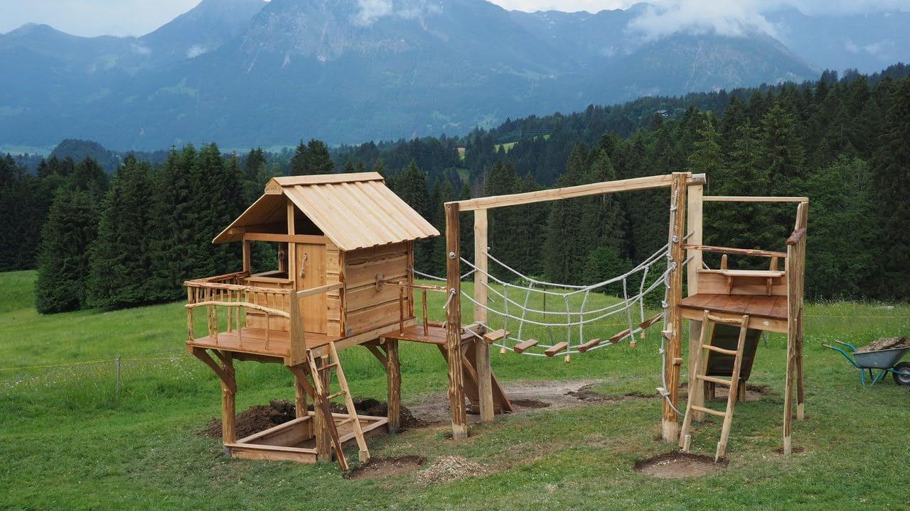 Naturholz Spielanlage auf der Alm vor Alpenkulisse